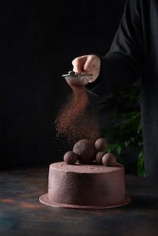 Donna versando il cacao in polvere su una torta al cioccolato, immagine di messa a fuoco selettiva