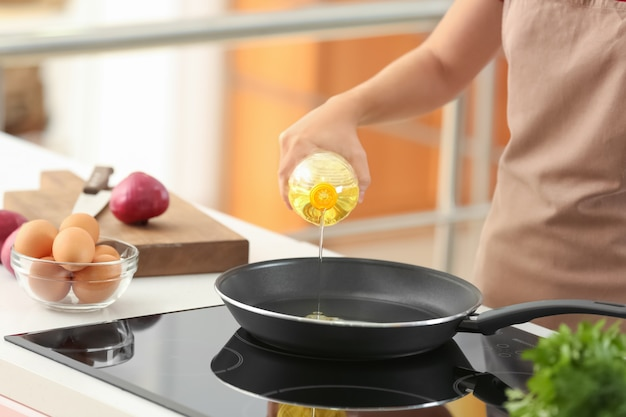 Donna che versa olio da cucina dalla bottiglia nella padella sul fornello