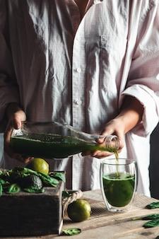 Donna che versa frullato verde e bianco appena miscelato in un barattolo di vetro con ingredienti intorno su un tavolo in legno rustico. mangiare sano e concetto di stile di vita. dieta disintossicante. idee per ricette.
