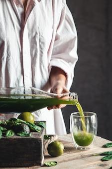 Donna che versa frullato verde e bianco appena miscelato in un barattolo di vetro con ingredienti intorno su un tavolo in legno rustico