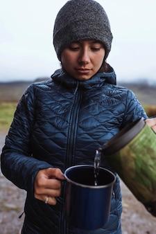Donna che versa acqua calda in una tazza