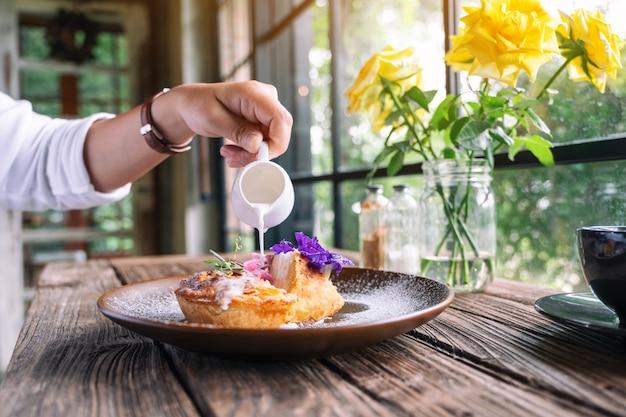 Una donna che versa il latte in un pezzo di torta di cocco con una bella decorazione in un piatto
