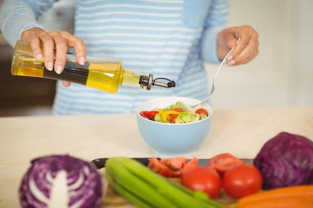 Olio di versamento della donna dentro ad una ciotola di insalata di verdure