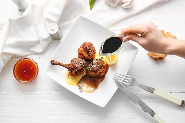 Donna che versa salsa su gustosi lecca-lecca di pollo sulla superficie in legno chiaro