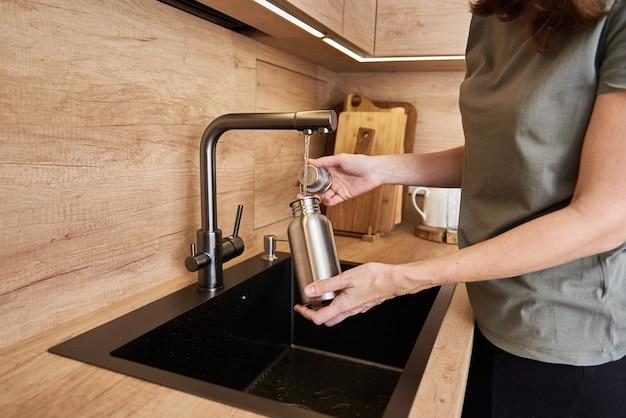 Donna che versa acqua in bottiglia eco-friendly in metallo. concetto di rifiuti zero