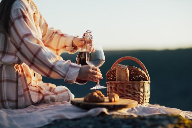 Donna che versa vino mentre è seduta al picnic