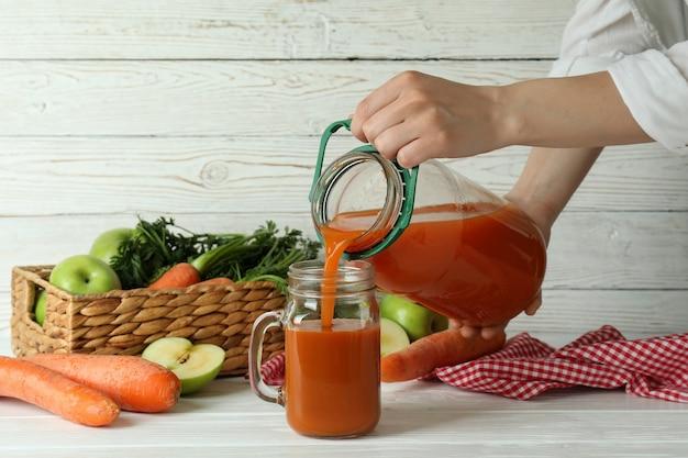 La donna versa il succo di carota della mela in un vaso su fondo isolato di legno bianco