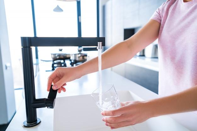 La donna versa l'acqua purificata filtrata fresca per bere da un rubinetto in un bicchiere in cucina a casa