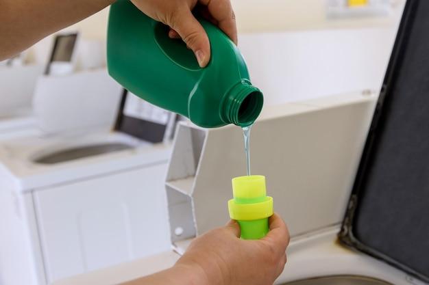 Una donna versa polvere liquida, versa balsamo, emolliente nella lavatrice.