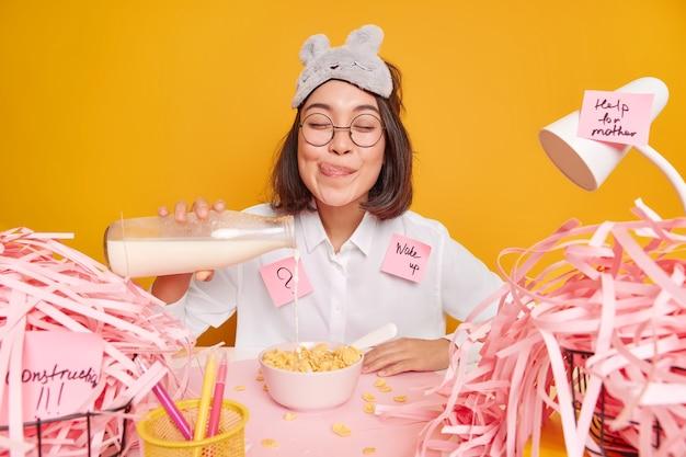 La donna versa il latte nei cereali andando a fare colazione lecca le labbra vestita con una camicia bianca e la maschera da notte posa al desktop su giallo