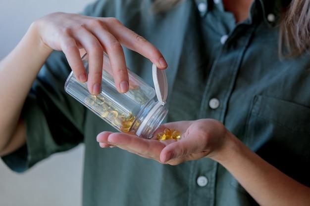 La donna versa da un vaso le pillole con olio di fegato di merluzzo. vista laterale