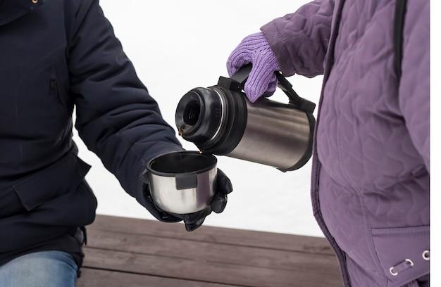 Una donna versa il tè da un thermos in una tazza thermos affinché un uomo possa bere e riscaldarsi.