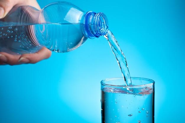 Una donna versa l'acqua in un bicchiere su sfondo blu.