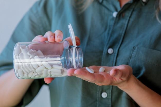 La donna versa le pillole bianche da un barattolo trasparente nella sua mano.
