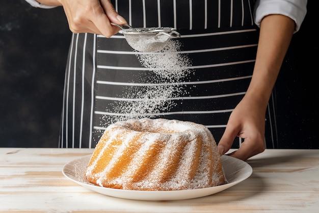 Donna in polvere di zucchero per ciambellone alla vaniglia su fondo di legno bianco
