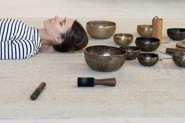 La donna pratica la meditazione con le campane tibetane, la terapia femminile che medita dal massaggio sonoro