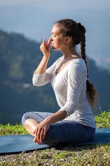 La donna pratica il pranayama nella posa del loto all'aperto
