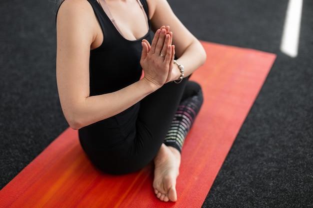 La donna pratica lo yoga sul tappetino