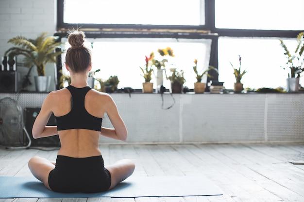 La donna pratica yoga e medita a casa.