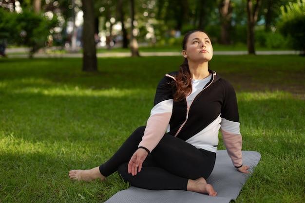 La donna pratica lo yoga nel parco sull'erba verde