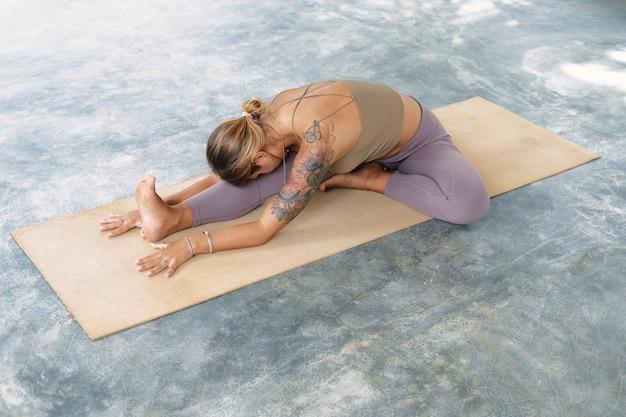 Donna che pratica yoga avanzato sulla stuoia organica