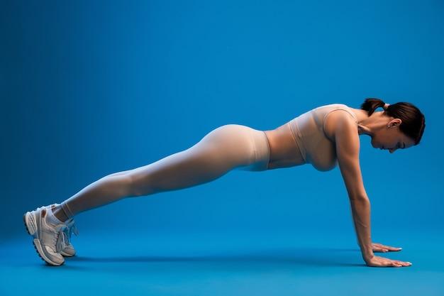 Donna che pratica posa di yoga kumbhakasana su superficie blu