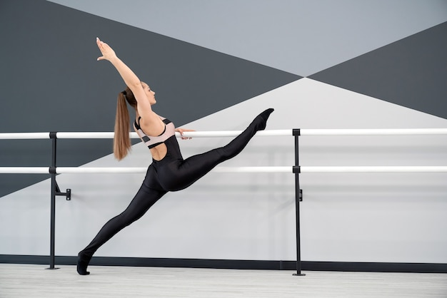 Donna pratica divisa tenendo i corrimani in studio di danza