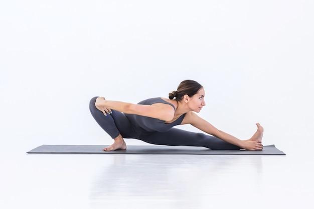 Donna che pratica yoga di allungamento sulla stuoia in sfondo bianco studio