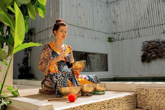 Donna che pratica con le campane tibetane