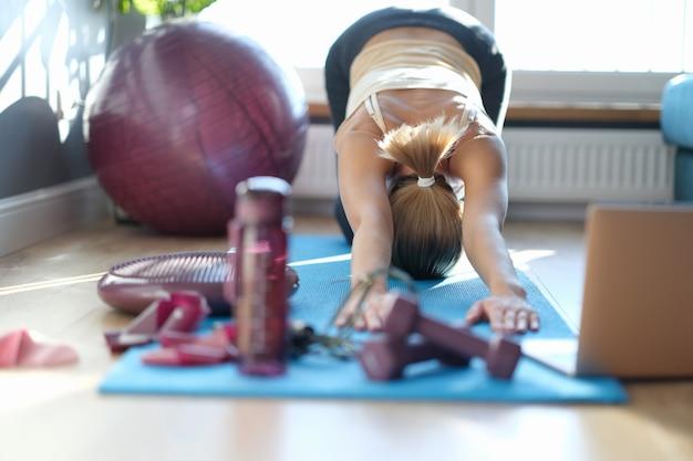 Donna che pratica yoga facendo esercizi per allungare la colonna vertebrale