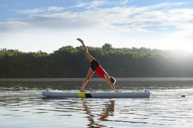 La donna a praticare yoga durante l'alba in paddle board
