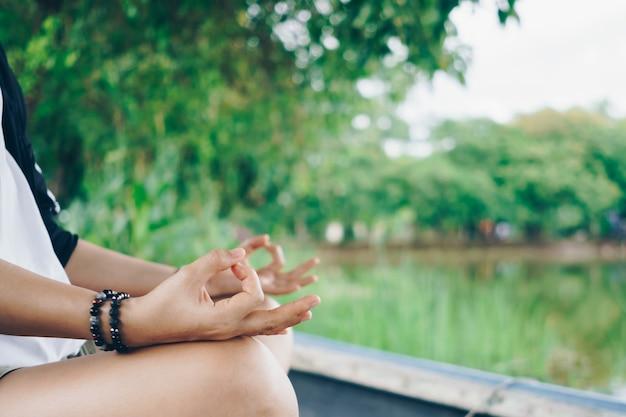 Donna che pratica lezione di yoga, respirazione, meditazione, all'aperto nel campo di erba. benessere, concetto di benessere