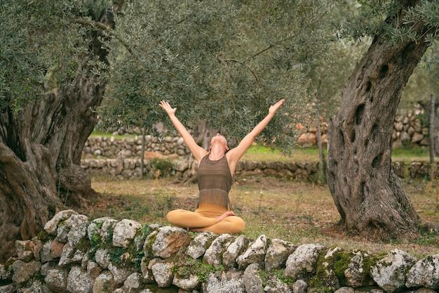 Donna che pratica yoga nella posa del loto nel parco