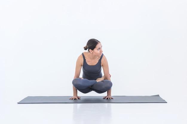 Donna che pratica yoga su un tappetino in studio in piedi sulle mani in posa
