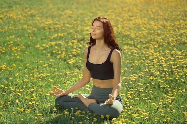 La donna a praticare yoga all'aperto in un parco