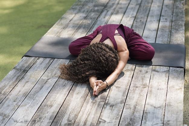 Una donna che pratica yoga, esegue un esercizio di balasana seduta su un tappetino nel parco, una posa da bambino