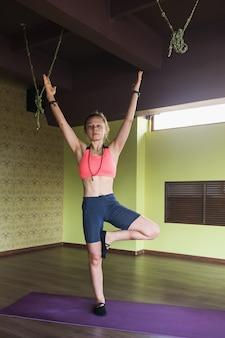La donna che pratica lo yoga esegue la posa dell'albero dell'esercizio vrikshasana con le braccia alzate