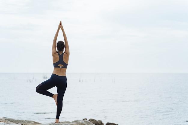 Una donna che pratica posture yoga sulla spiaggia Foto Premium