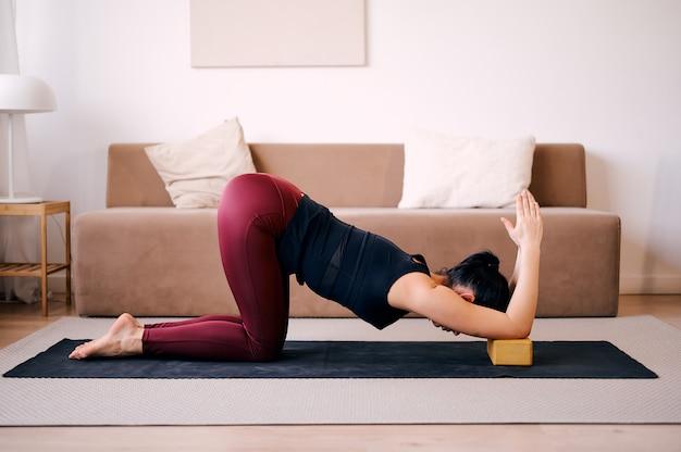 Yoga di pratica della donna che allunga facendo uso dei blocchi di legno
