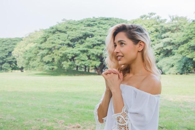 Donna che prega al mattino nel parco. cristianesimo fede speranza amore concetto.