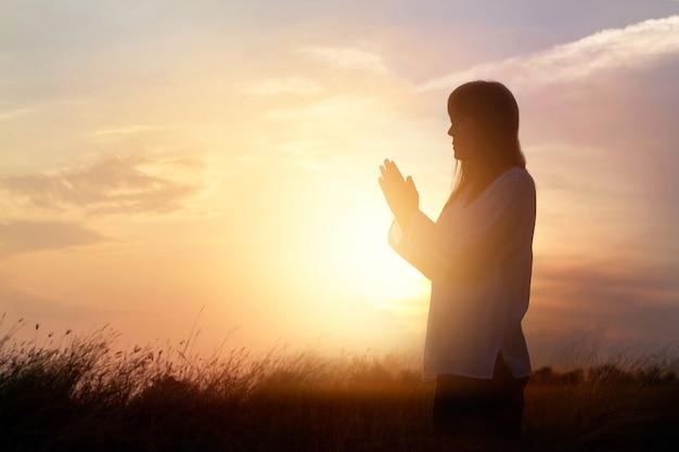 Donna che prega e che pratica meditando sul fondo di tramonto della natura, concetto di speranza