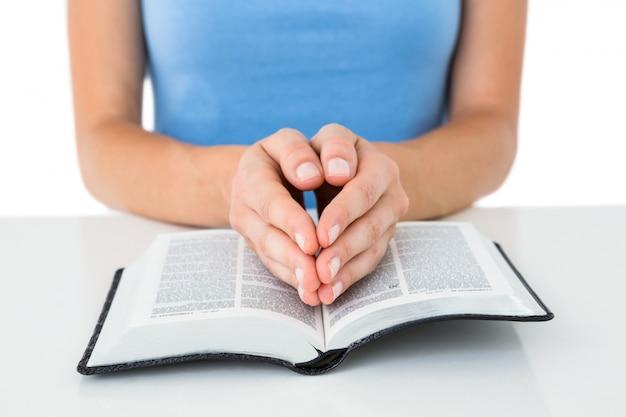 Donna che prega mentre leggendo la bibbia