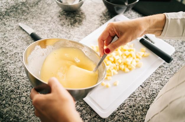 Una donna prepara gli ingredienti per preparare un pan di spagna nella sua cucina di casa