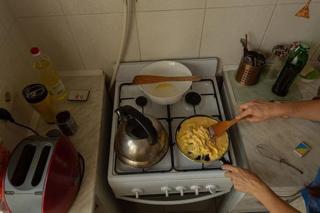 La donna prepara una frittata su un fornello a gas.