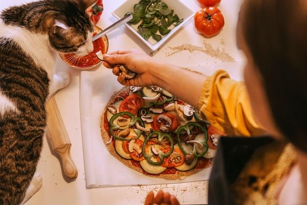 Donna che prepara una deliziosa pizza con il suo dolce gatto. concetto fatto in casa.
