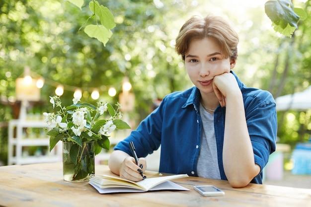 Donna che prepara per l'esame. ritratto all'aperto di una giovane donna sicura che scrive nel blocchetto per appunti