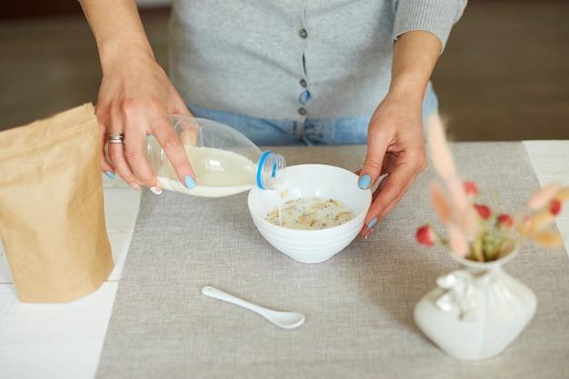 Donna che prepara una sana colazione a casa, mano femminile che tiene la bottiglia versando il latte in una ciotola di fiocchi di cereali muesli con uvetta semi di noci, farina d'avena cibo muesli, concetto di stile di vita