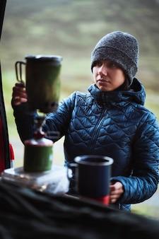 Donna che prepara acqua calda per il caffè mattutino