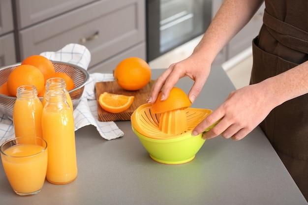 Donna che prepara il succo d'arancia in cucina