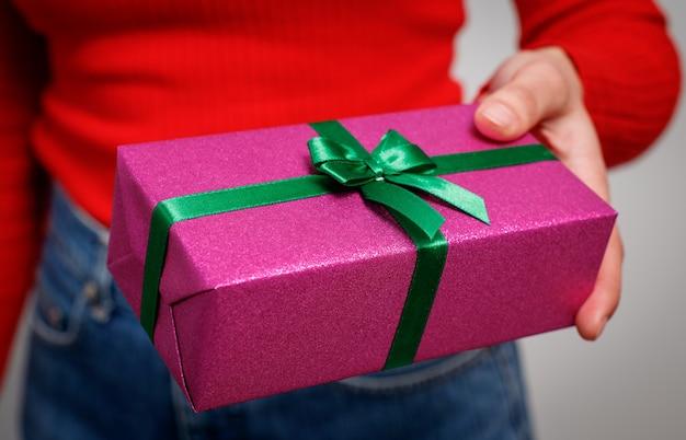 La donna presenta un regalo per natale in una confezione regalo luminosa. avvicinamento.